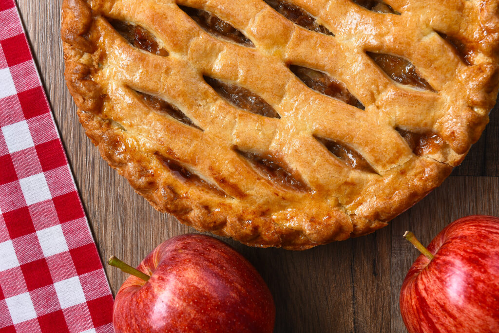 Flat Lay view of a fresh baked apple pie with apples on a rustic wood table.