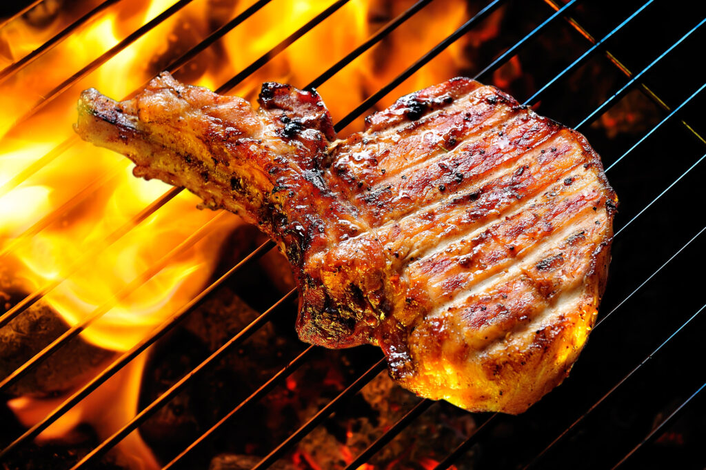 Grilled pork steak on the grill.