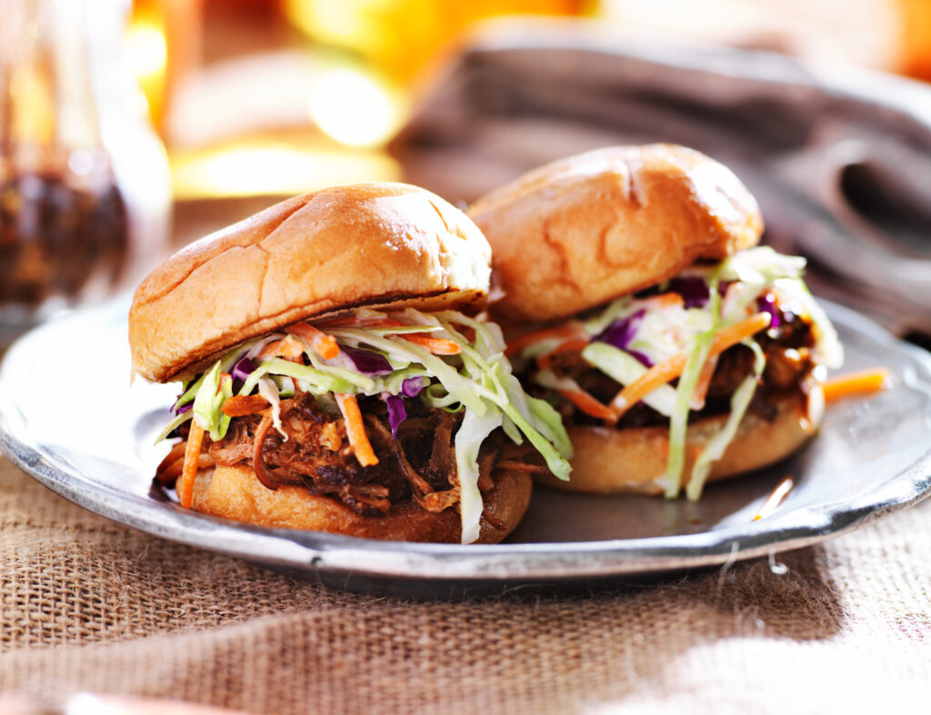 Pulled pork sandwiches with bbq sauce and slaw on a silver plate.