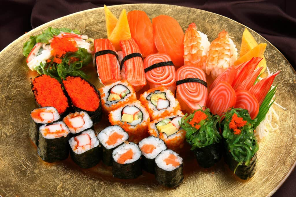 Assorted, colorful Sushi rolls on a gold plate.