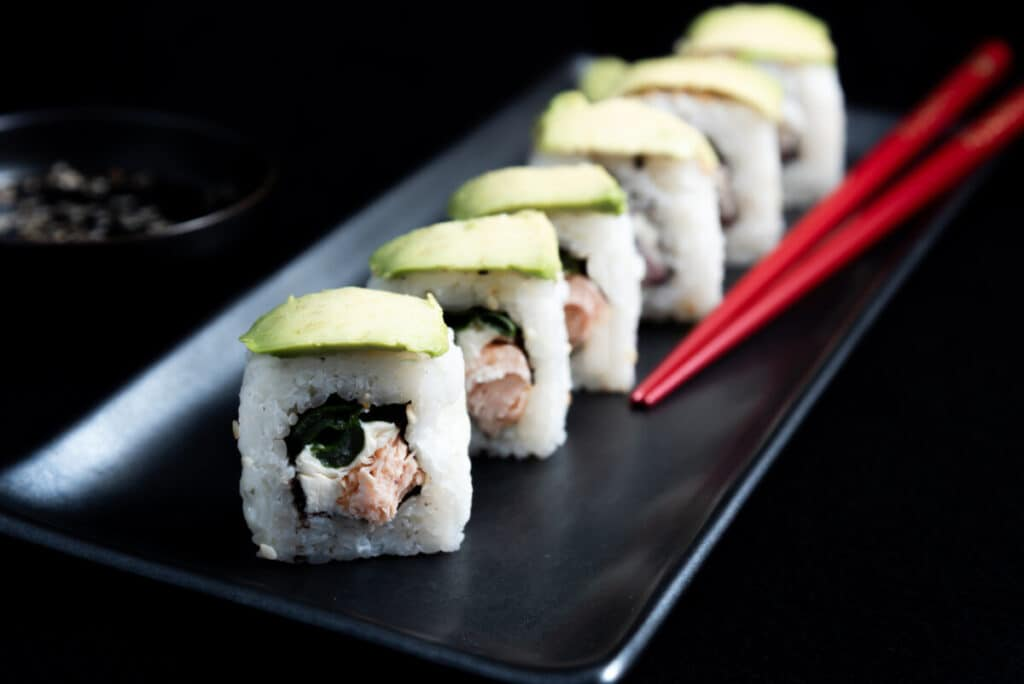 Sushi roll with avocado wrap, grilled salmon, Philadelphia cheese and green onions on black plate and red chopsticks. Small pot with soy sauce. Black background.