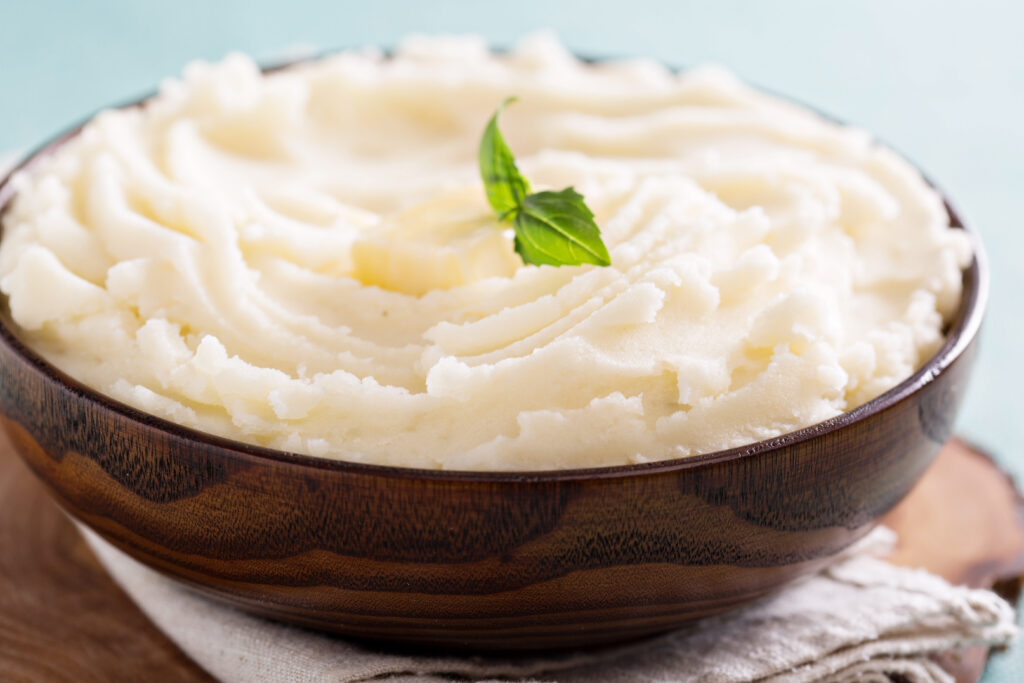 Mashed potatoes in a big wooden bowl.
