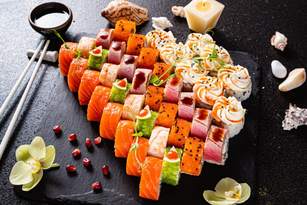 Assorted sushi, soy sauce, and chopsticks set on a black background.