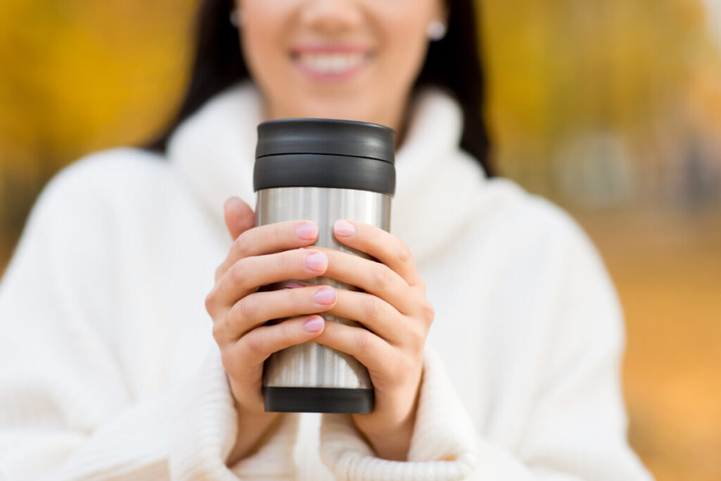 Close up of happy young woman drinking hot chocolate from thermos or tumbler in autumn park